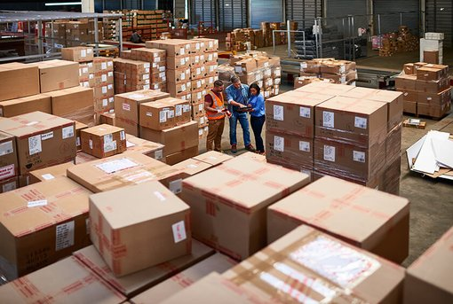 three people talking in middle of warehouse filled with boxes