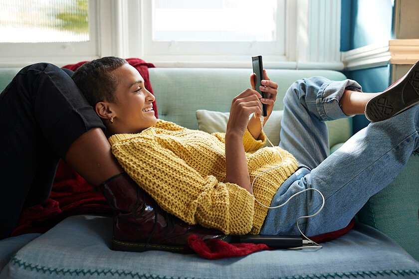 woman laying on couch looking at phone